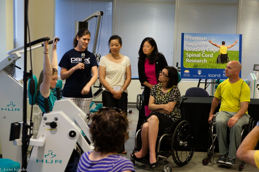 PARC participant and Spinal Cord Injury BC staff member Kirsten Sharp demonstrates some of the PARC equipment as PARC Coordinator Megan Brousseau describes the equipment and exercise.