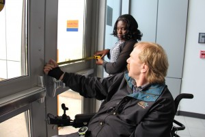 Accessibility Team members Stan (left) and Laetitia (right) measure the width of a door during an accessibility assessment.