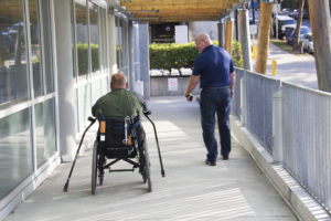 Two men move down a ramp side-by-side. One in a wheelchair, the other ambulatory.
