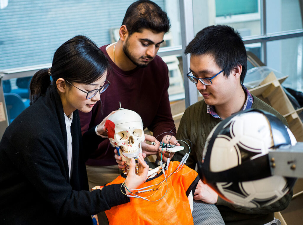 Pictured: Dr. Wu and two students infront of a dummy with a soccer ball in the foreground